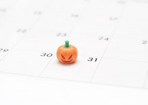 Closeup of a mass produced Jack O'Lantern toy on a calendar marking Halloween.